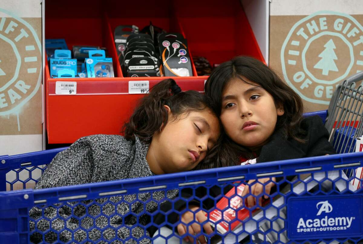 """Ten-year-old Ashley Castillo, left, sleeps on her sister's, Daisy, shoulder as their family shopped at the Academy Sports + Outdoors store during Black Friday Friday, Nov. 23, 2018, in Spring, Texas. The two girls were excited to go shopping after winning six dollars in a game of """"La Loteria"""" after Thanksgiving dinner at their grandmother's home. """"So far they haven't spend any of it,"""" said their mother, Rosa Castillo.The family had been out shopping since 10 p.m. Thursday."""