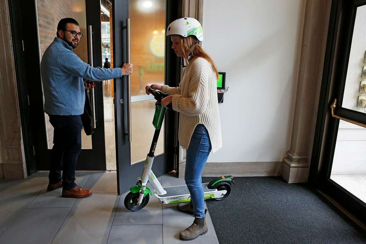 From left: Lime's Joe Arellano and Emma Green take the new Lime-S Gen 3 into their headquarters on Tuesday, Dec. 4, 2018, in San Francisco, Calif. Lime's headquarters is located at 85 Second St.