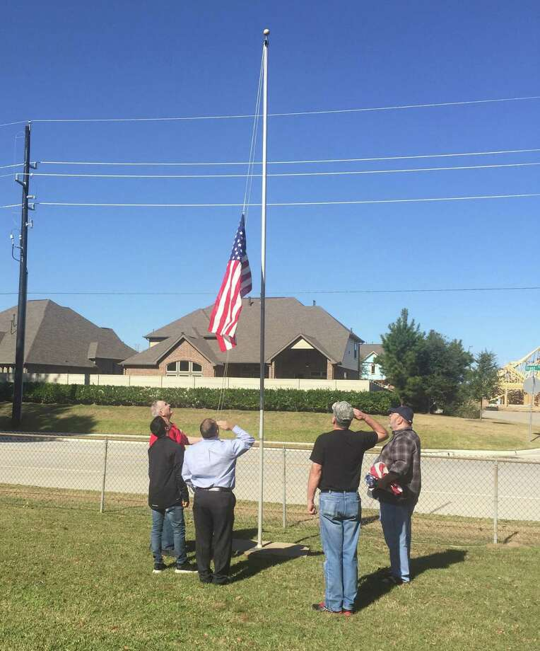"A New Flag at Magnolia Cemetery: Attendees at a Dec. 2 planning meeting at Magnolia Cemetery in Katy for the Dec. 15 ""Wreaths Across America"" ceremony took time to remove a faded American flag and hoist a new one provided by American Legion Post 164."