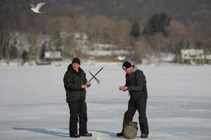 Karol Polowski, left, of Plainview, and Greg Linnhoff, of New Hartford, rig the tip-up while ice fishing on Lake Waramaug in Kent, Conn. on Sunday, Feb. 9, 2014.