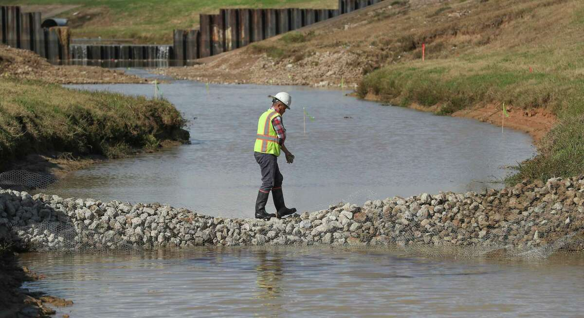 A worker crosses a temporary silt dam as the Harris County Flood Control District repairs damage caused by Hurricane Harvey near Fry Road and Bear Creek Friday, Nov. 30, 2018, in Katy.