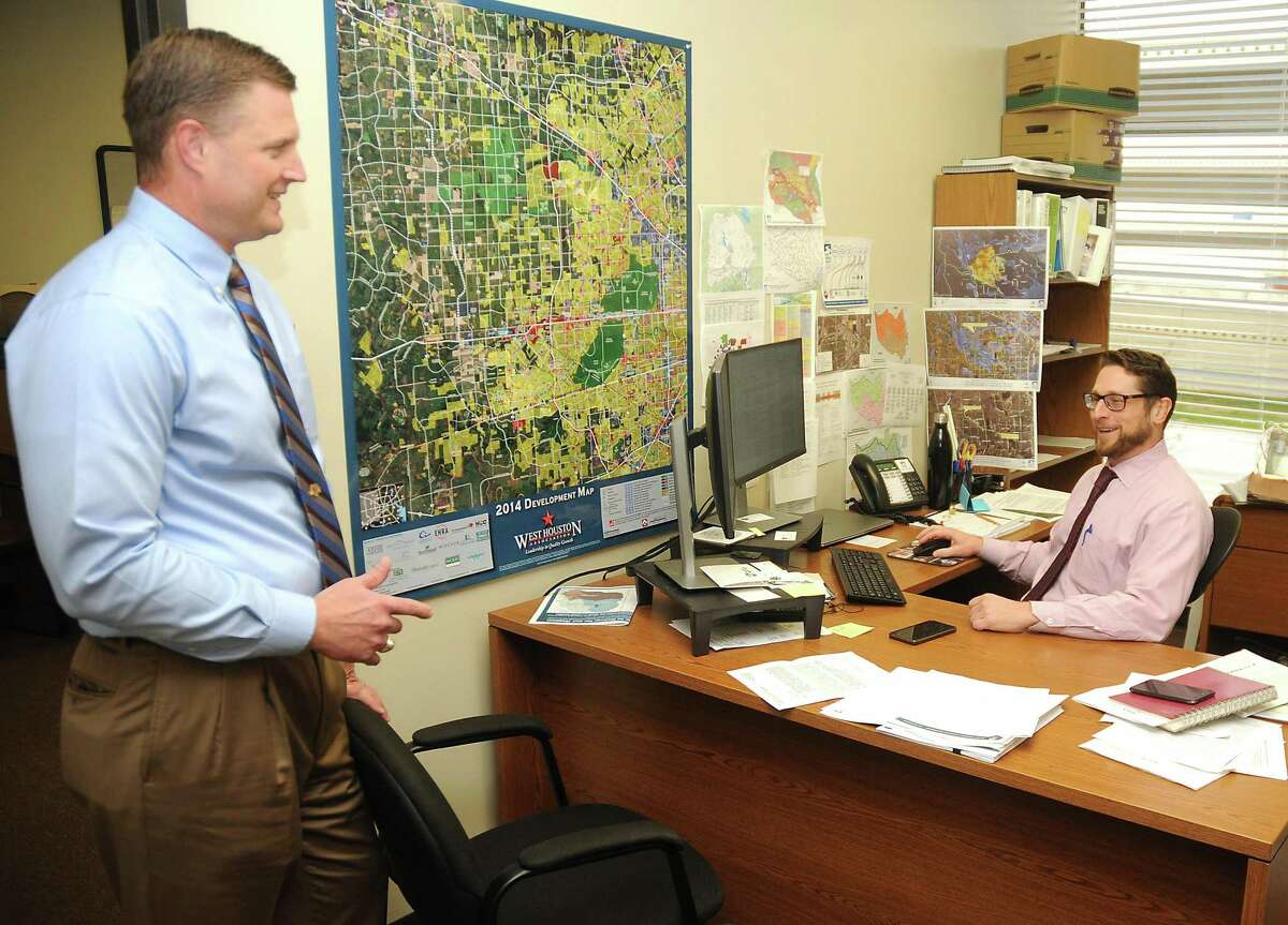 Russ Poppe, executive director of the Harris County Flood Control District, at left, talks with Matthew Zeve at the office Thursday Dec. 06,2018.