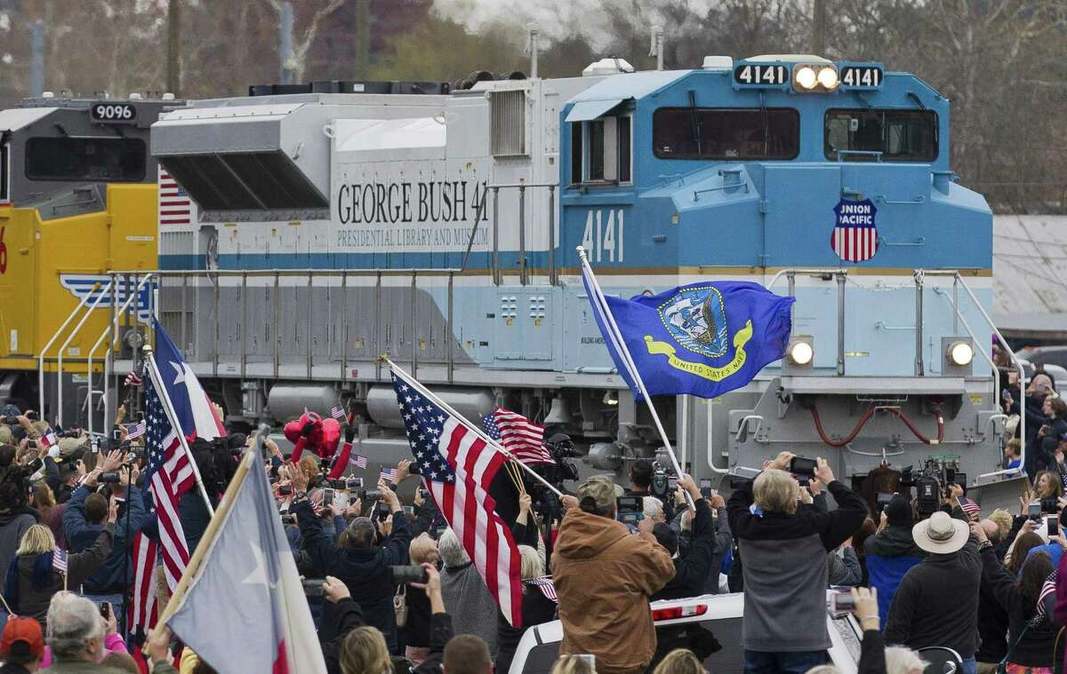 """Onlookers watch as a Union Pacific train led by a locomotive dubbed """"Bush 4141"""" carries the body of the late President George H.W. Bush through Magnolia."""