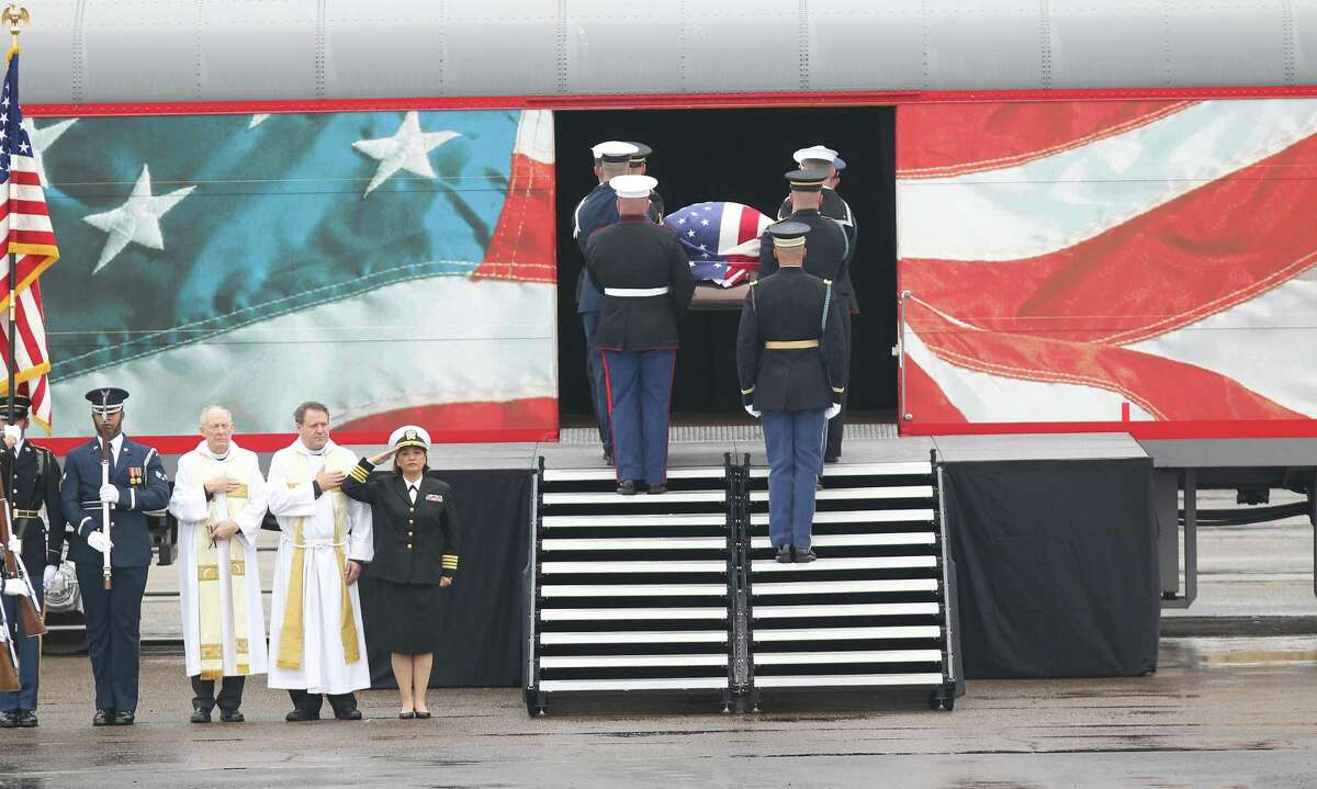 The casket of George H.W. Bush is lifted onto the George Bush 4141 train at the Union Pacific Railroad Westfield Auto Facility.