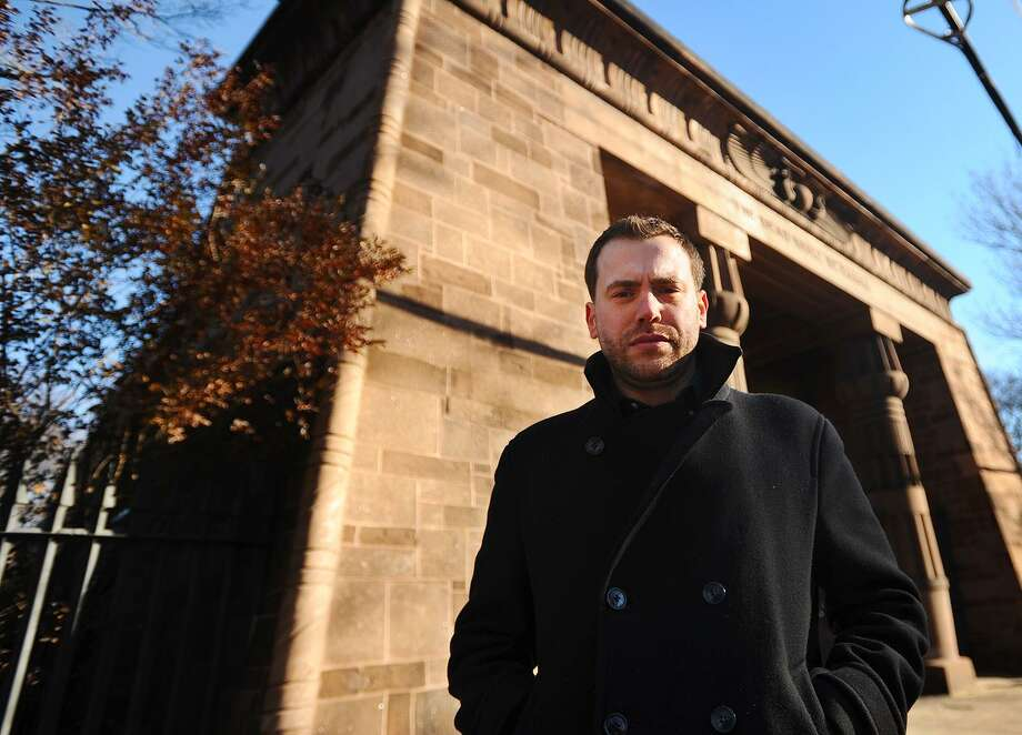 """Dion Baia outside the Egyptian entry arch at the Grove Street Cemetery in New Haven, site of a scene from his new novel, """"Blood in the Streets."""" Photo: Brian A. Pounds / Hearst Connecticut Media / Connecticut Post"""