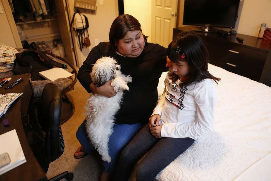 Ximena Rodriguez comforts her 9-year-old daughter, Isabella Rodriguez, alongside their dog, Branny, at their home in San Ramon. Photo: Santiago Mejia / The Chronicle