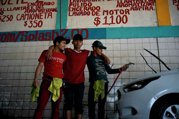 """In this Nov. 27, 2018 photo, migrants Nelson Landaverde, left, Angel Lemus, center, and Erick Canales, who traveled with a caravan of Central American migrants, pose for a photo at their new job as car washers, in Tijuana, Mexico. """"Here you make a little money, I can take something to eat to my baby,"""" said Landaverde, a 21-year-old from Copan, Honduras. Landaverde and his pregnant wife have already put their names on an informal list to apply for asylum in the U.S., but in the meantime he wants to earn money to make their lives a little more comfortable in Tijuana."""