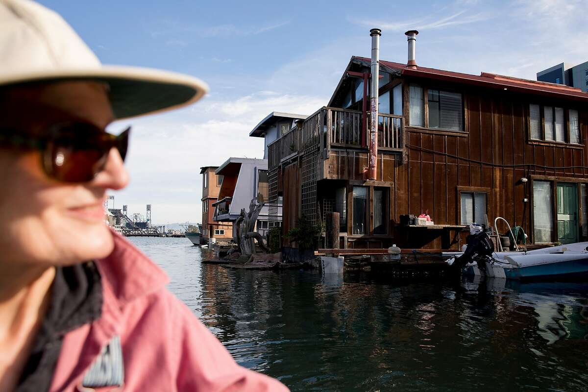 Ginny Stearns rows a small boat past the home she shares with her husband, Bob Isaacson, in the Mission Creek Harbor community in San Francisco, Calif. on Friday, Dec. 7, 2018.