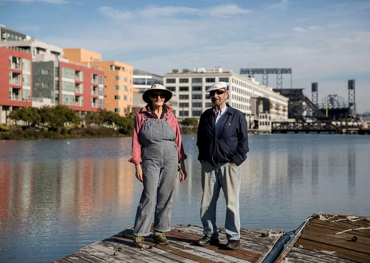 Ginny Stearns (left) and Bob Isaacson pose for a portrait on the dock near their floating home in the Mission Creek Harbor community in San Francisco, Calif. on Friday, Dec. 7, 2018.