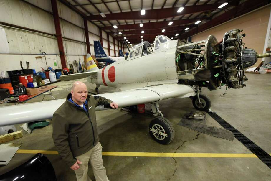 "Integra Optics CEO David Prescott stands next to his Tora 101 Japanese Zero movie replica that he restoring at owned by  hanger in a hanger at Albany International Airport on Friday, Dec. 7, 2018, in Colonie, N.Y.  The aircraft was once used by the Canadian military before being converted to appear in three Hollywood films, including ""Tora! Tora! Tora!""*, ""Midway"" and ""Baa Baa Blacksheep.O  The aircraft was converted from a Canadian Car & Foundry Harvard IV. (Will Waldron/Times Union) Photo: Will Waldron / 20045656A"