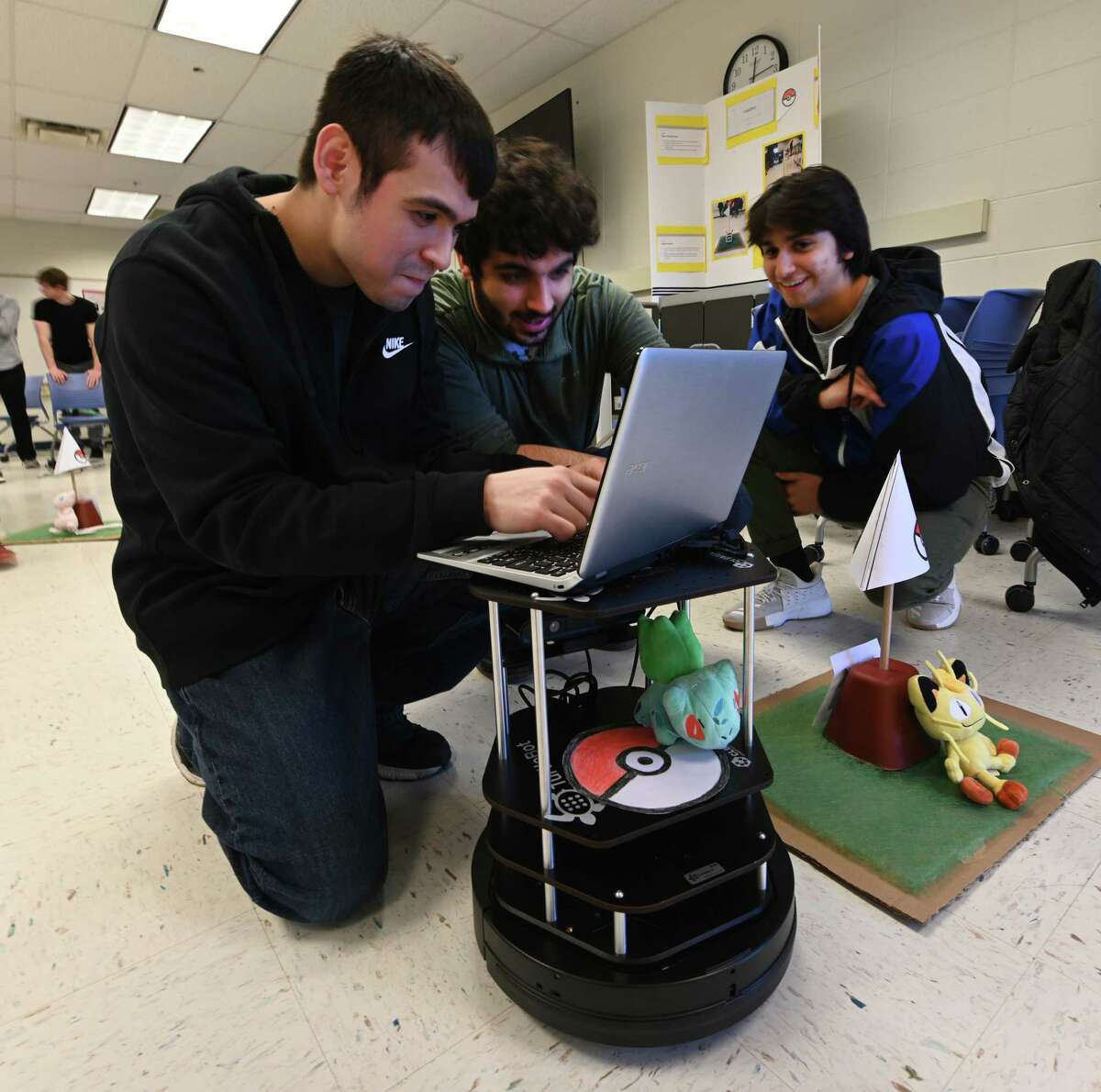 Javier Rodriguez, left, Robert Morvillo, center, and Daniel Van Dyk fine tune their robot Pokebot during the Robo Show held at Siena College Friday Dec. 7, 2018 in Loudonville, N.Y. The group built the robot to mimic a warehouse security bot for their school project in robotics. (Skip Dickstein/Times Union)