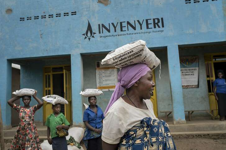 Mukamurenzi Anasthasie leaves an Inyenyeri store with a bag of wood pellets for her stove from the company in western Rwanda, Oct. 4, 2018. Inyenyeri's founder is betting his wood-pellet stove � and his company's distribution system � can make billions by rescuing some of the poorest people on earth from toxic smoke. (Diana Zeyneb Alhindawi/The New York Times)