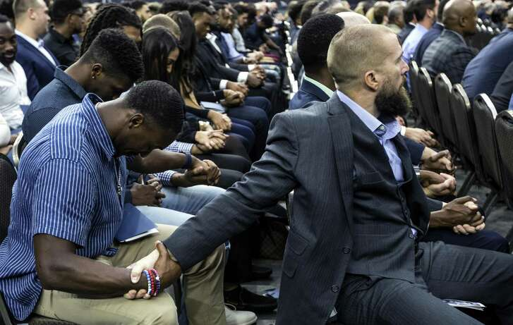 Friday's public memorial service was an emotional one, especially for members of the Texans, including Luke Richesson, senior director of sports performance, who shares a moment with defensive back Andre Hal, left.