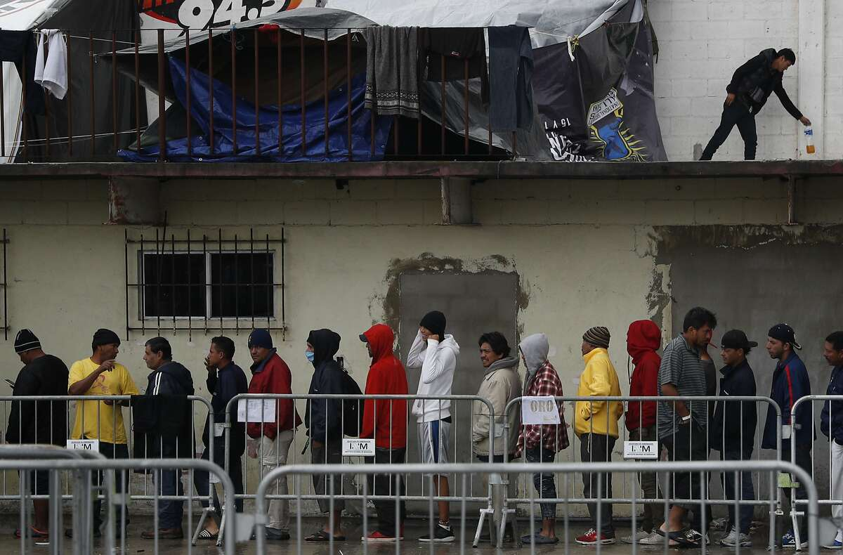 Migrants wait in line to receive free breakfast inside the Barretal migrant shelter, a former concert venue, in Tijuana, Mexico, Thursday, Dec. 6, 2018. Thousands of migrants on the Mexico side of the border are living in crowded tent cities in Tijuana after a grueling weeks-long journey through Mexico on foot and hitching rides with the goal of applying for asylum in the U.S. (AP Photo/Rebecca Blackwell)