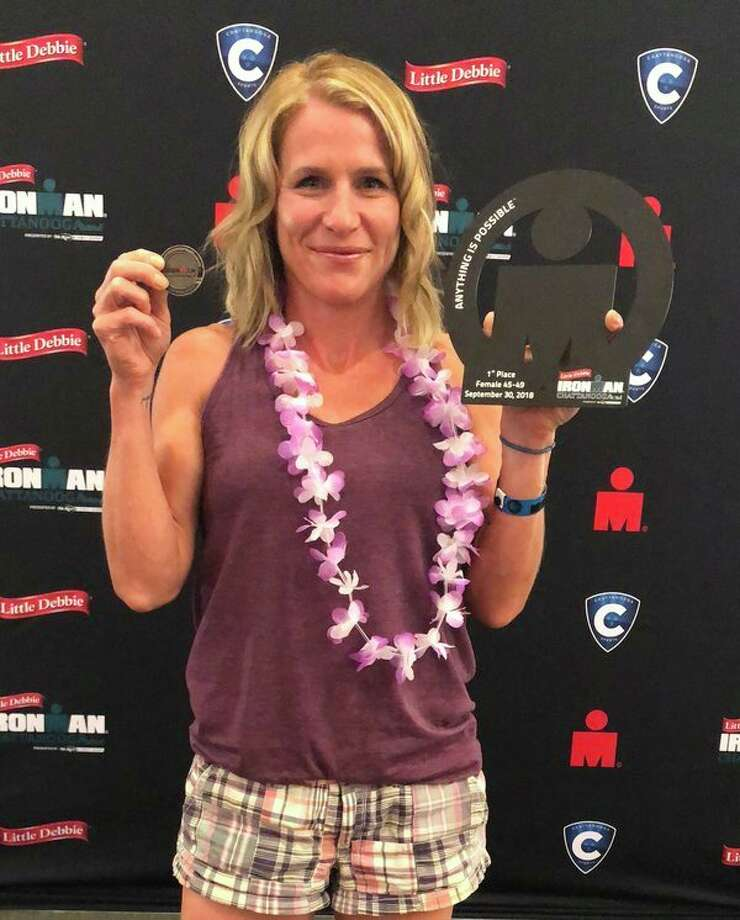 Midland's Maggie Rettelle stands with her World Championship coin and her first-place award after winning her age group at Ironman Chattanooga on Sept. 30. (Photo by Chris Swiecicki)