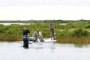 Anglers fish along an Espiritu Santo Bay shoreline where stands of black mangrove, a tropical shrub that has significantly expanded its range as winters warm, are displacing oyster grass-dominated salt marsh and altering the dynamics and productivity of Texas' coastal ecosystems.