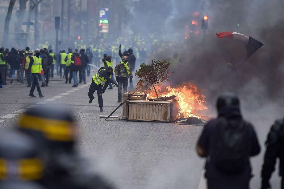 """Protestors wearing """"Yellow vests"""" (gilets jaunes) clash with riot police amid tear gas near the Champs Elysees in Paris on December 8, 2018 during a protest of against rising costs of living they blame on high taxes. - Paris was on high alert on December 8 with major security measures in place ahead of fresh """"yellow vest"""" protests which authorities fear could turn violent for a second weekend in a row. (Photo by Lucas BARIOULET / AFP)LUCAS BARIOULET/AFP/Getty Images Photo: LUCAS BARIOULET;Lucas Barioulet / AFP / Getty Images"""