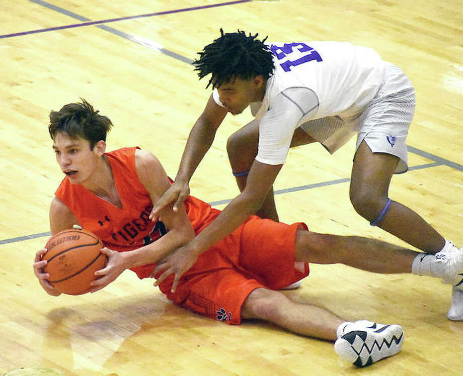 Edwardsville's Brennan Weller shields the ball away from Collinsville's Ray'Sean Taylor in the third quarter of Friday night's loss to the Kahoks at Vergil Fletcher Gym. Photo: Matt Kamp | For The Telegraph