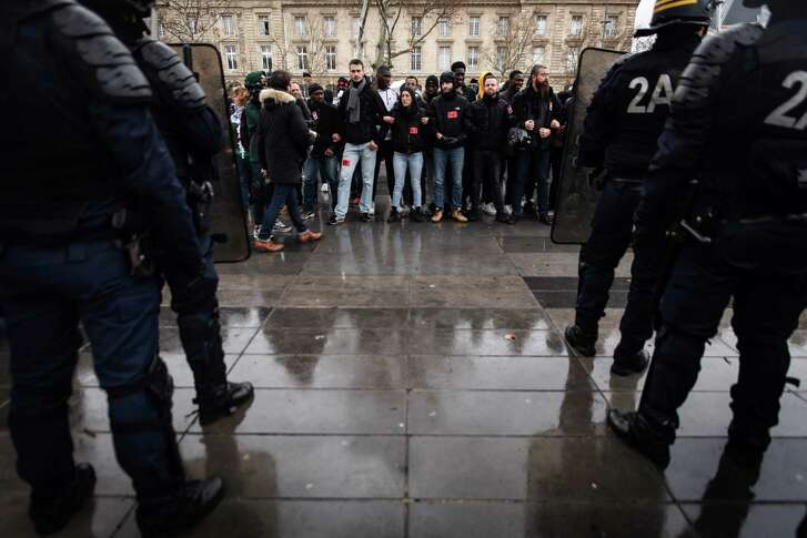 French anti-riot police officers stand gaurd in fornt of high school students in the place de la Republique in Paris during a demonstration on December 7, 2018 to protest against the different education reforms including the overhauls and stricter university entrance requirements. - Images of dozens of high-school pupils kneeling with their hands behind their heads during mass round-ups sparked an outcry on December 7, 2018. Protests at some 280 schools have added to a sense of general revolt in France.