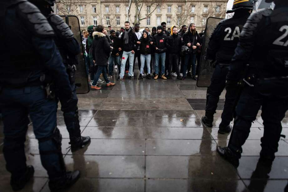French anti-riot police officers stand gaurd in fornt of high school students in the place de la Republique in Paris during a demonstration on December 7, 2018 to protest against the different education reforms including the overhauls and stricter university entrance requirements. - Images of dozens of high-school pupils kneeling with their hands behind their heads during mass round-ups sparked an outcry on December 7, 2018. Protests at some 280 schools have added to a sense of general revolt in France. Photo: LIONEL BONAVENTURE, Contributor / AFP/Getty Images / Philippe LOPEZ