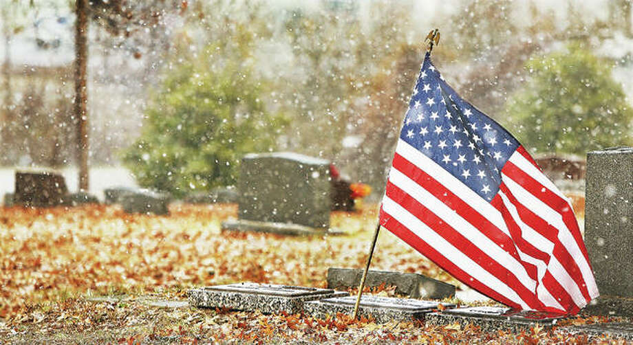 A larger-sized flag flies Thursday over the grave of a 23-year-old U.S. Navy ensign who died during World War II, as the snow blows through the Upper Alton Cemetery. Friday was the 77th anniversary of the Japanese attack on the U.S. Naval Base at Pearl Harbor which killed 2,335 American servicemen, 2,008 of those were Navy personnel. The attack launched the U.S. into the second World War. Photo: John Badman | The Telegraph