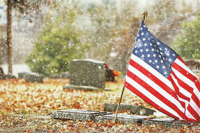 A larger-sized flag flies Thursday over the grave of a 23-year-old U.S. Navy ensign who died during World War II, as the snow blows through the Upper Alton Cemetery. Friday was the 77th anniversary of the Japanese attack on the U.S. Naval Base at Pearl Harbor which killed 2,335 American servicemen, 2,008 of those were Navy personnel. The attack launched the U.S. into the second World War.
