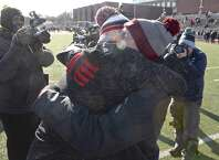 Greenwich head coach John Marinelli gets a hug from his father New Canaan head coach Lou Marinelli, right, after defeating his fathers team 34-0 in the Connecticut high school Class LL football championship game between Greenwich and New Canaan high schools, Saturday morning, December 8, 2018, at Boyle Stadium, Stamford High School, Stamford, Conn.