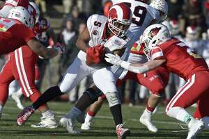 New Canaan's J.R. Moore (5) runs into Greenwich's Evan Weiold (2) in the Connecticut high school Class LL football championship game between Greenwich and New Canaan high schools, Saturday morning, December 8, 2018, at Boyle Stadium, Stamford High School, Stamford, Conn.