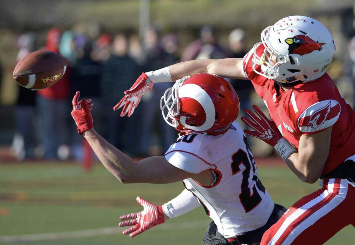 Greenwich's Hunter Cusimano (1) knocks away a pass intended for New Canaan's Quintin O'Connell (20) in the Class LL football championship game on Saturday morning at Boyle Stadium at Stamford High School.