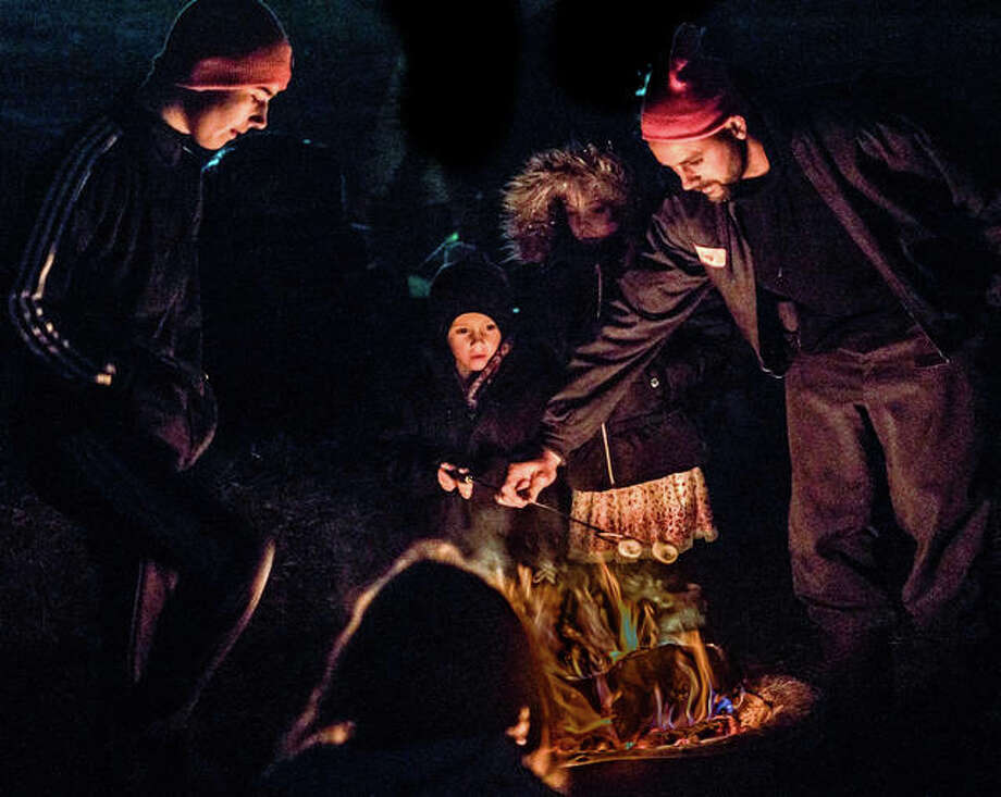 A family roasts marshmallows Friday night in Godfrey's Glazebrook Park during the annual Snowflake Festival. The open fire was a welcome amenity, as temperatures for the event dipped into the low 20s. Photo: Nathan Woodside | The Telegraph