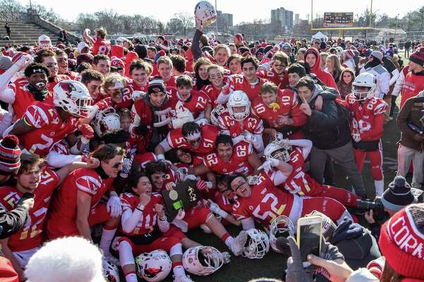 Greenwich High School Football piles up for a team photo with their Championship plaque after the Class LL State Championship game between on New Canaan and Greenwich on December 8, 2018 at Boyle Stadium in Stamford, CT.