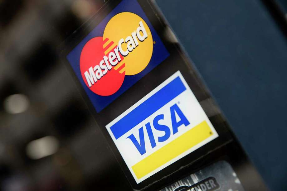 FILE- This Nov. 29, 2018, file photo shows credit card logos posted on a store's door in Philadelphia. Trying to get your first credit card can be as frustrating as trying to land your first job. Employers want experience, but you can't get experience unless someone hires you. Similarly, a credit card is the quickest way to build a good credit history, but without a good credit history it's hard to get a credit card. (AP Photo/Matt Rourke, File) Photo: Matt Rourke / Copyright 2018 The Associated Press. All rights reserved.