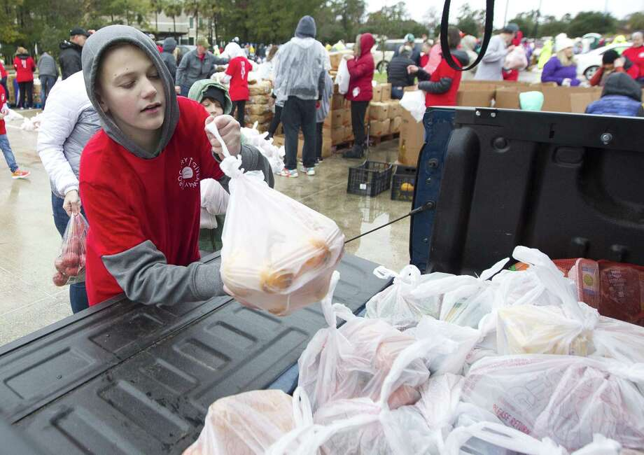 Matthew Larkin helps load groceries as he and more than 1,000 volunteers helped give away 180,000 pounds of food to local residents in need during The Ark Churchs annual grocery giveaway, Saturday, Dec. 8, 2018, in Conroe. Photo: Jason Fochtman, Houston Chronicle / Staff Photographer / © 2018 Houston Chronicle