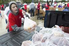 Matthew Larkin helps load groceries as he and more than 1,000 volunteers helped give away 180,000 pounds of food to local residents in need during The Ark Churchs annual grocery giveaway, Saturday, Dec. 8, 2018, in Conroe.
