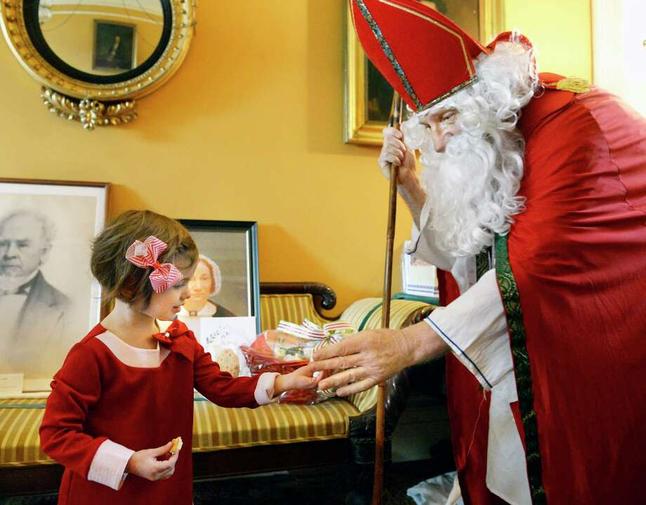 Three-year-old Hazel Nolan of Albany gets a treat from Sinterklaas at the historic Ten Broeck Mansion during a holiday open house Saturday Dec. 8, 2018 in Albany, NY.  (John Carl D'Annibale/Times Union) Photo: John Carl D'Annibale / 20045663A