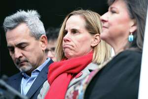 Michael Song, left, and his wife, Kristin, center, listen to speakers at a news conference about gun safety in front of First Congregational Church in Guilford Nov. 27.  At right is the Rev. Ginger Brasher-Dunningham.