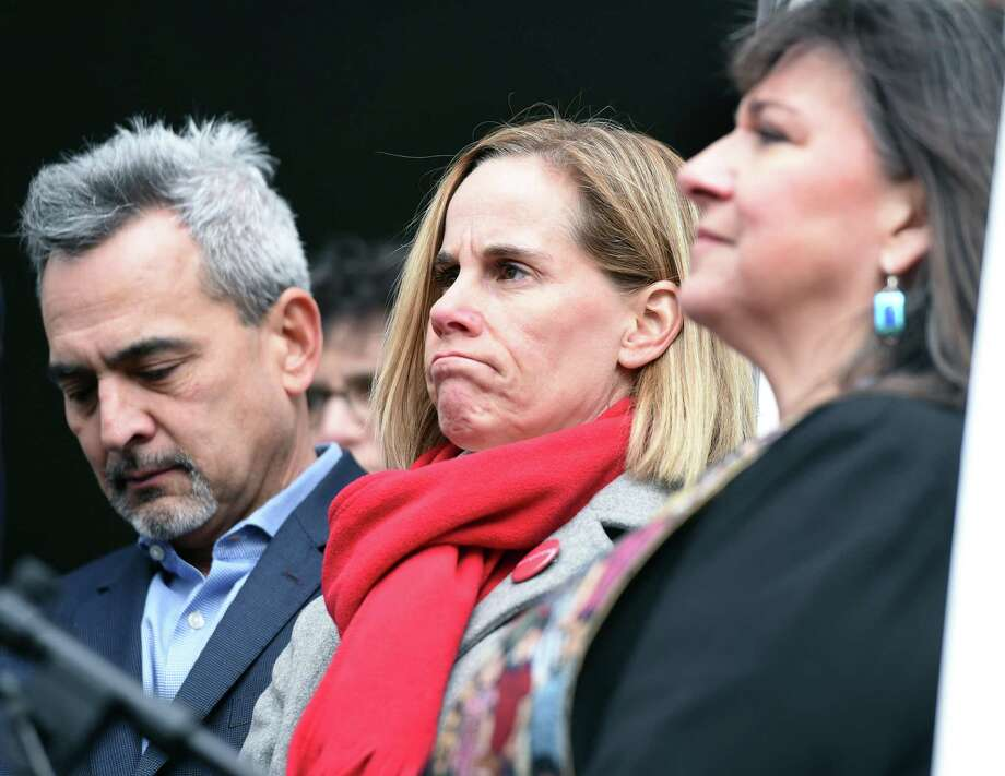 Michael Song, left, and his wife, Kristin, center, listen to speakers at a news conference about gun safety in front of First Congregational Church in Guilford Nov. 27.  At right is the Rev. Ginger Brasher-Dunningham. Photo: Arnold Gold / Hearst Connecticut Media File / New Haven Register