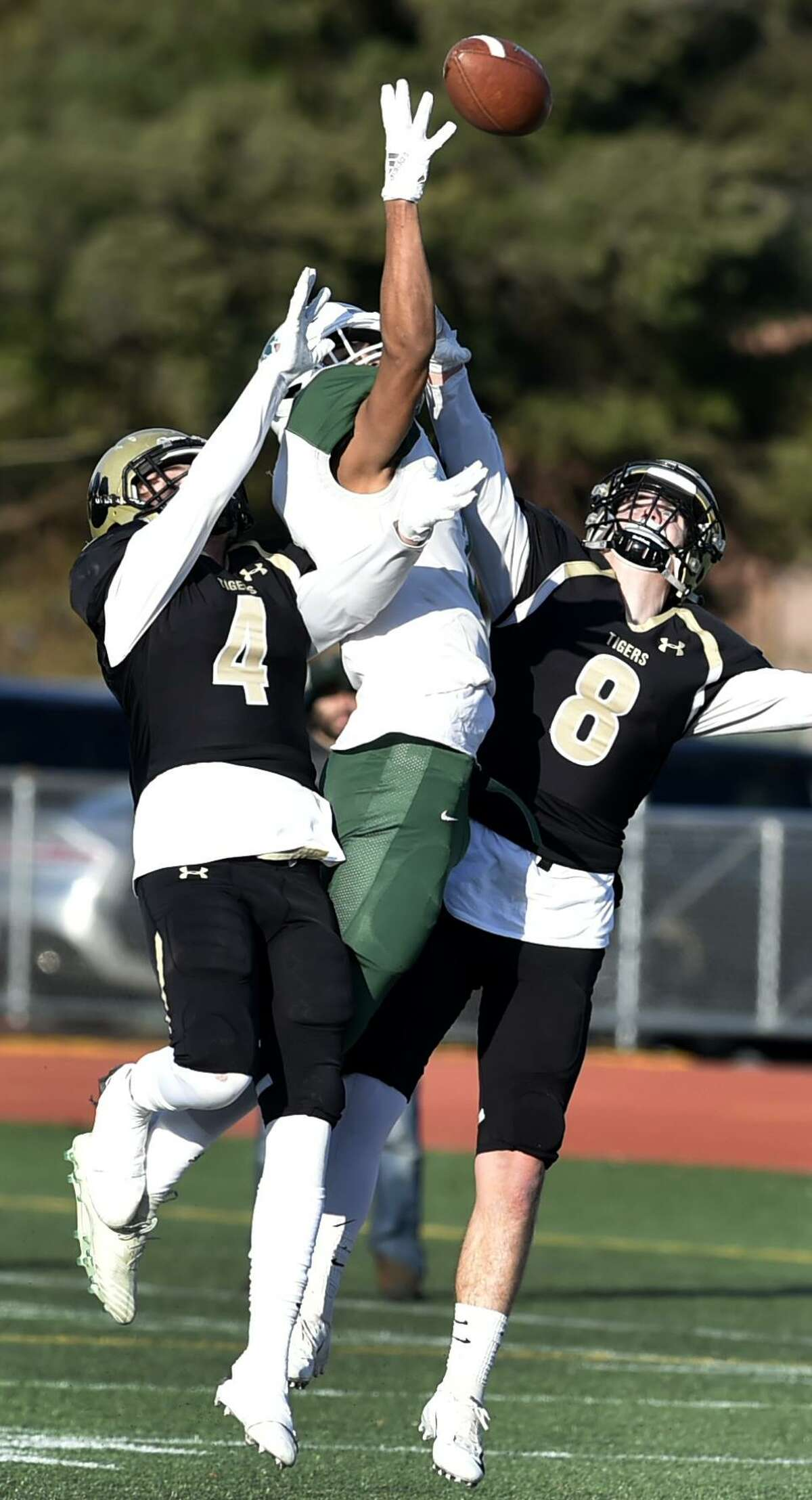 Hand's Ian Butler, right, intercepts a pass against Maloney's Victor Marquez, center as Hand's Thomas Ferrick assists on the play on Saturday.