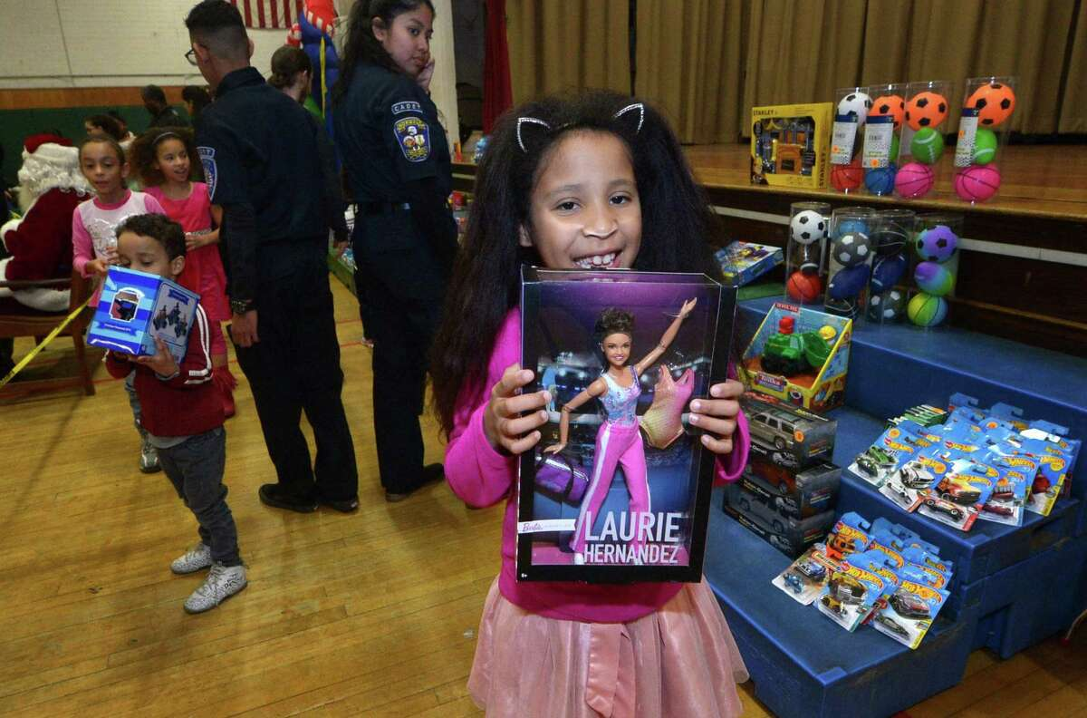 Katalina Richeme, 9, enjoy her gift Saturday, December 8, 2018, during The Norwalk Community Police Children?'s Holiday Party Saturday at Columbus Magnet School in Norwalk, Conn. The event provided gifts for over 100 needy children.