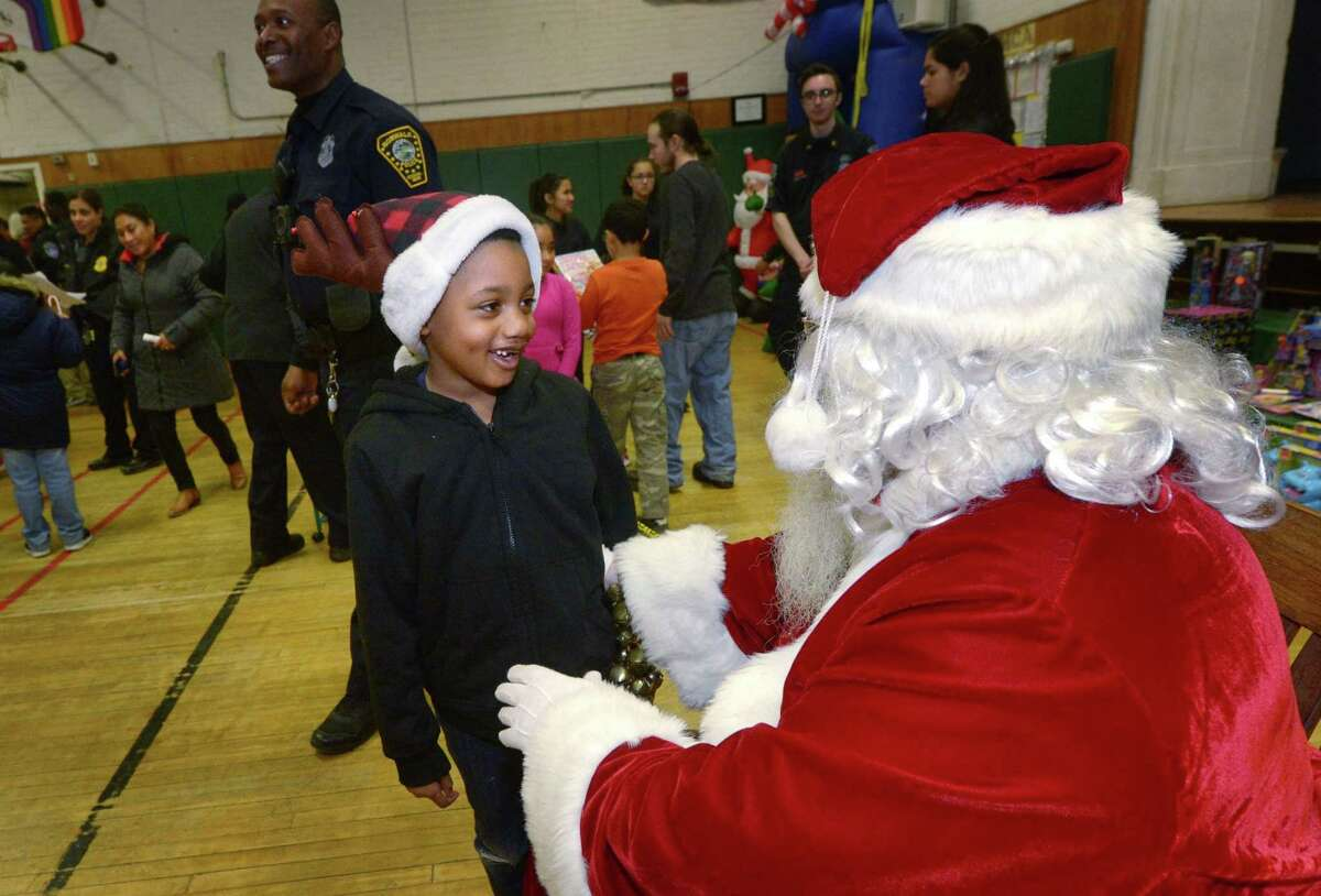 Tyler Geneus, 6, greets Santa Claus, aka retired police officer Joe Kubik, Saturday, December 8, 2018, during The Norwalk Community Police Childrens Holiday Party Saturday at Columbus Magnet School in Norwalk, Conn. The event provided gifts for over 100 needy children.