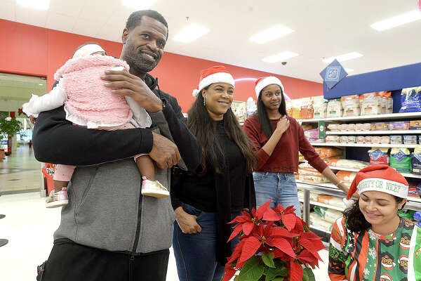 Stephen Jackson holds a shopper's baby as he talks with volunteers at the sign in table during his Christmas with a Champion event at Target Saturday. The Port Arthur native and former NBA champion donated gift cards to 100 families to purchase gifts for the holidays. Photo taken Saturday, December 8, 2018 Kim Brent/The Enterprise