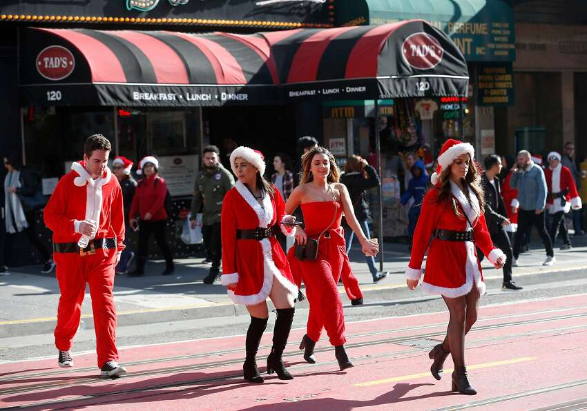 Revelers dressed as Santa Claus cross Powell Street near Union Square for the annual SantaCon in San Francisco, Calif. on Saturday, Dec. 8, 2018. The event was held despite the denial of a permit issued by the city.