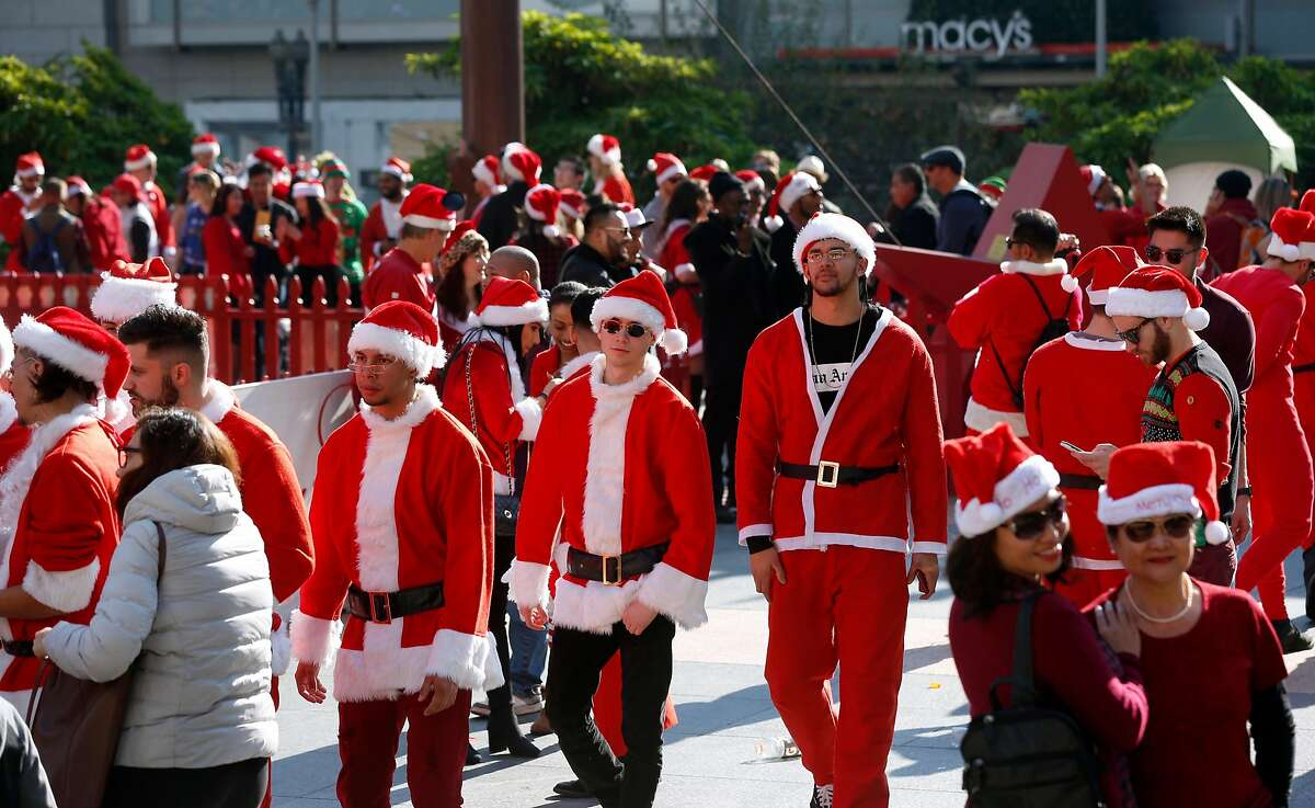 Costumed revelers wander through Union Square for the annual SantaCon gathering in San Francisco, Calif. on Saturday, Dec. 8, 2018. The event was held despite the denial of a permit issued by the city.
