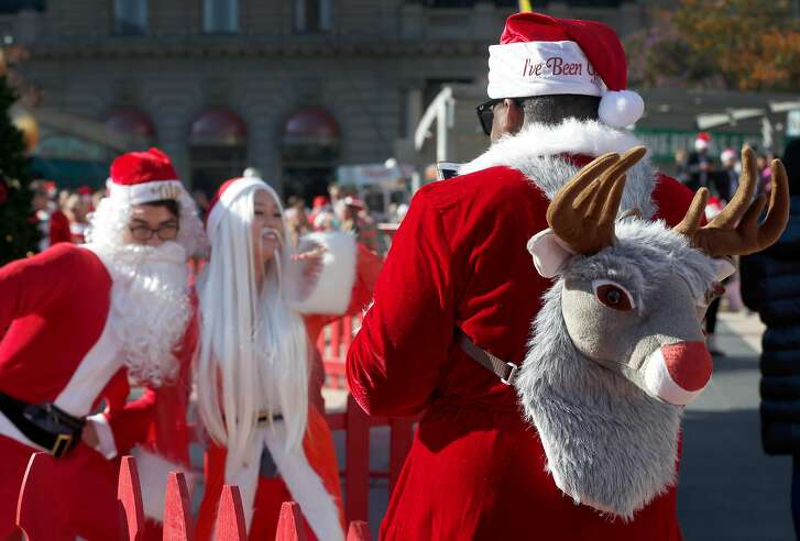 Michael Bozman takes a photo of friends at the annual SantaCon gathering at Union Square in San Francisco, Calif. on Saturday, Dec. 8, 2018. The event was held despite the denial of a permit issued by the city.