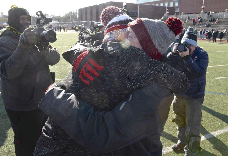 Greenwich coach John Marinelli gets a hug from his father, New Canaan coach Lou Marinelli, right, after defeating his father's team 34-0 in the Class LL championship Saturday. Photo: H John Voorhees III / Hearst Connecticut Media / The News-Times