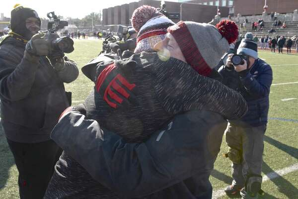 Greenwich coach John Marinelli gets a hug from his father, New Canaan coach Lou Marinelli, right, after defeating his father's team 34-0 in the Class LL championship Saturday.