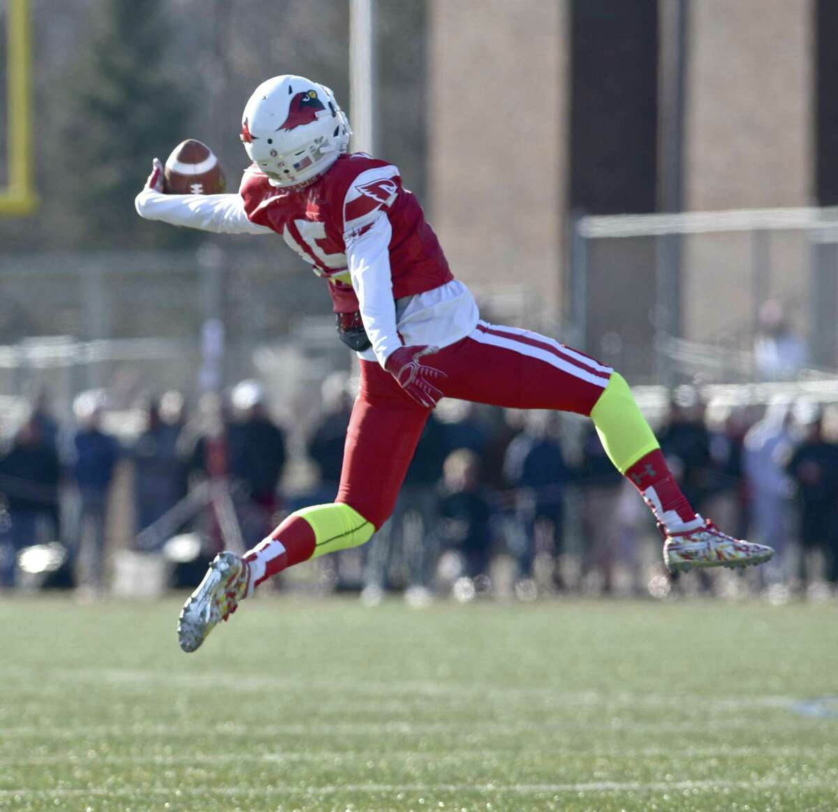 Greenwich's A.J. Barber reaches back to grab the ball during a trick play, after which he threw a touchdown pass, in Saturday's Class LL championship against New Canaan.