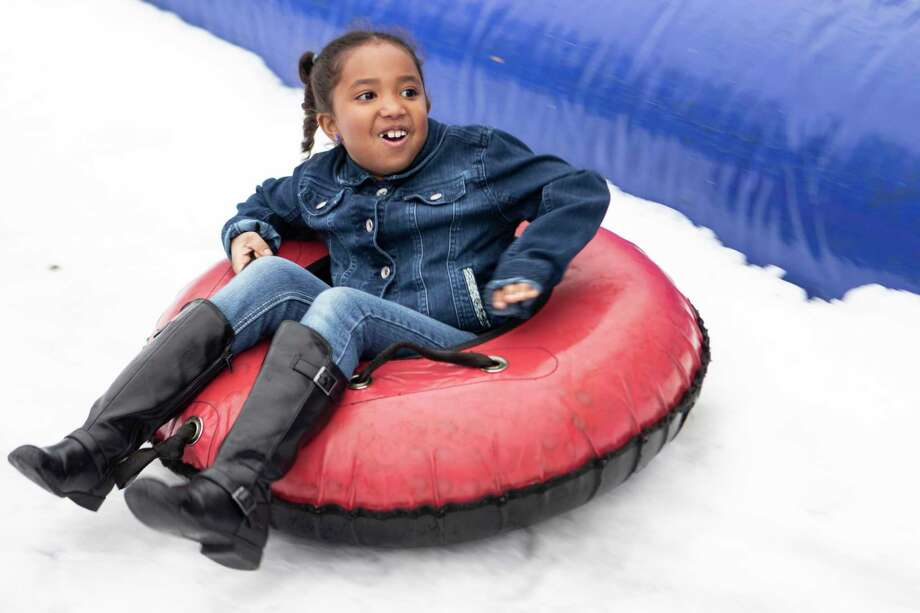 Mia Chernitsky, 7, comes down a snow slide during the Conroe Christmas Celebration on Saturday in Conroe. Photo: Cody Bahn, Houston Chronicle / Staff Photographer / © 2018 Houston Chronicle
