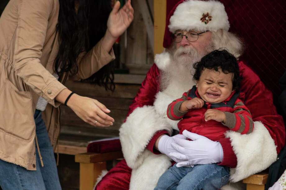Noah Zamora, 1, begins to cry after Conroe resident Nicole Gavidia places him on Santa Claus' lap during the Conroe Christmas Celebration on Saturday, Dec. 8, 2018 in Conroe. This year's celebration is set for Saturday from 11 a.m. to 4 p.m. at Heritage Place Park. Photo: Cody Bahn, Houston Chronicle / Staff Photographer / © 2018 Houston Chronicle