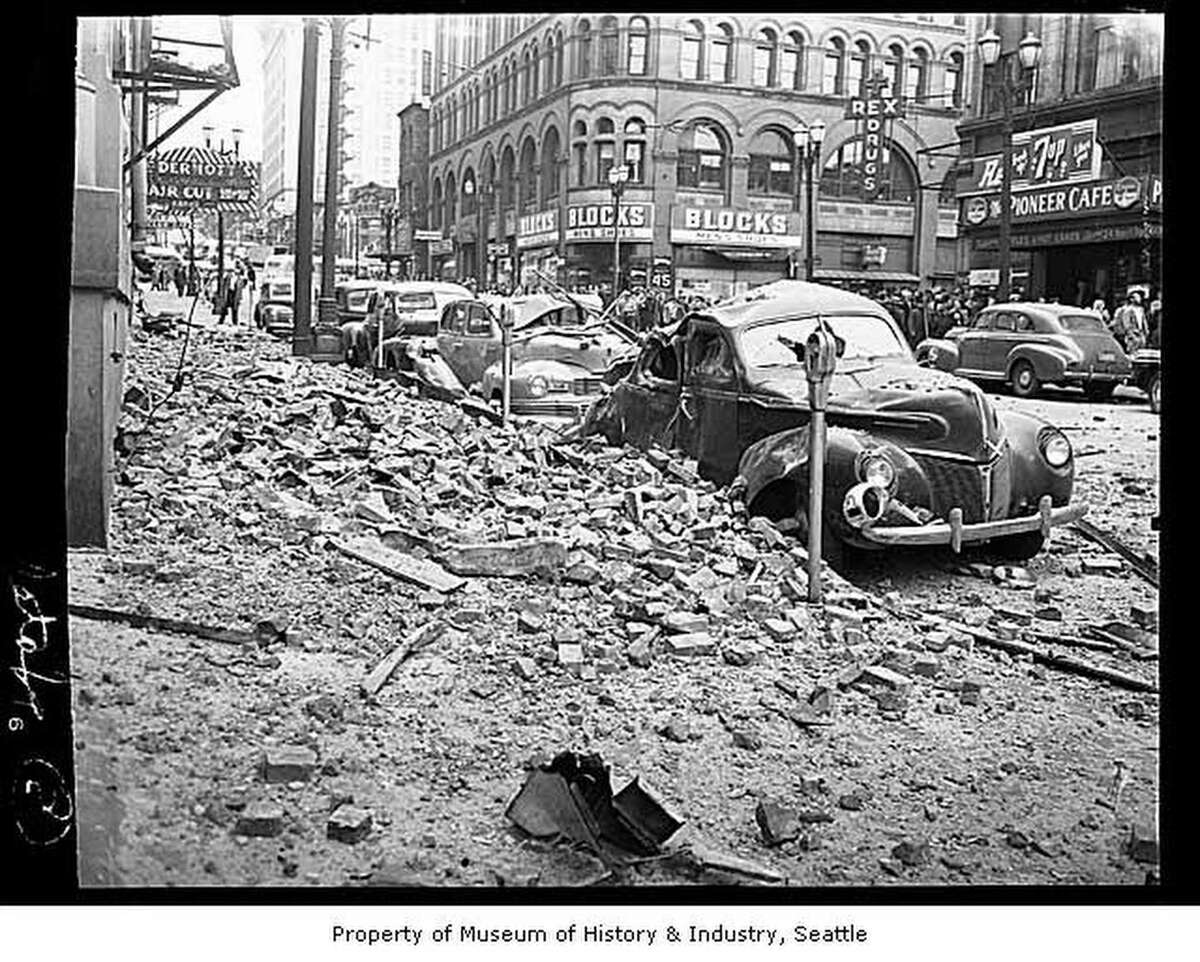 Shortly before noon on Wednesday, April 13, 1949, an earthquake rocked the area from British Columbia to Oregon and caused extensive damage. Seven people died and at least 64 were injured in the heaviest shock ever recorded in the region. In Seattle, downtown streets and buildings were jammed with people but no deaths occurred. As soon as the ground began to shake, photographer Ken Harris headed out the door for Pioneer Square, where he predicted damage would be extensive. His front page photo shows the bricks that cascaded from the cornice of the Seattle Hotel at First and Yesler Way, damaging at least five automobiles. At least a half a dozen buildings in the Pioneer Square area had damage to cornices or walls.